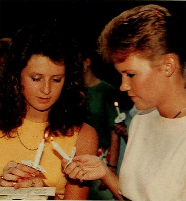 Michelle Leary, '92 helps a fellow classmate light her candle during the Honor Code Ceremony.